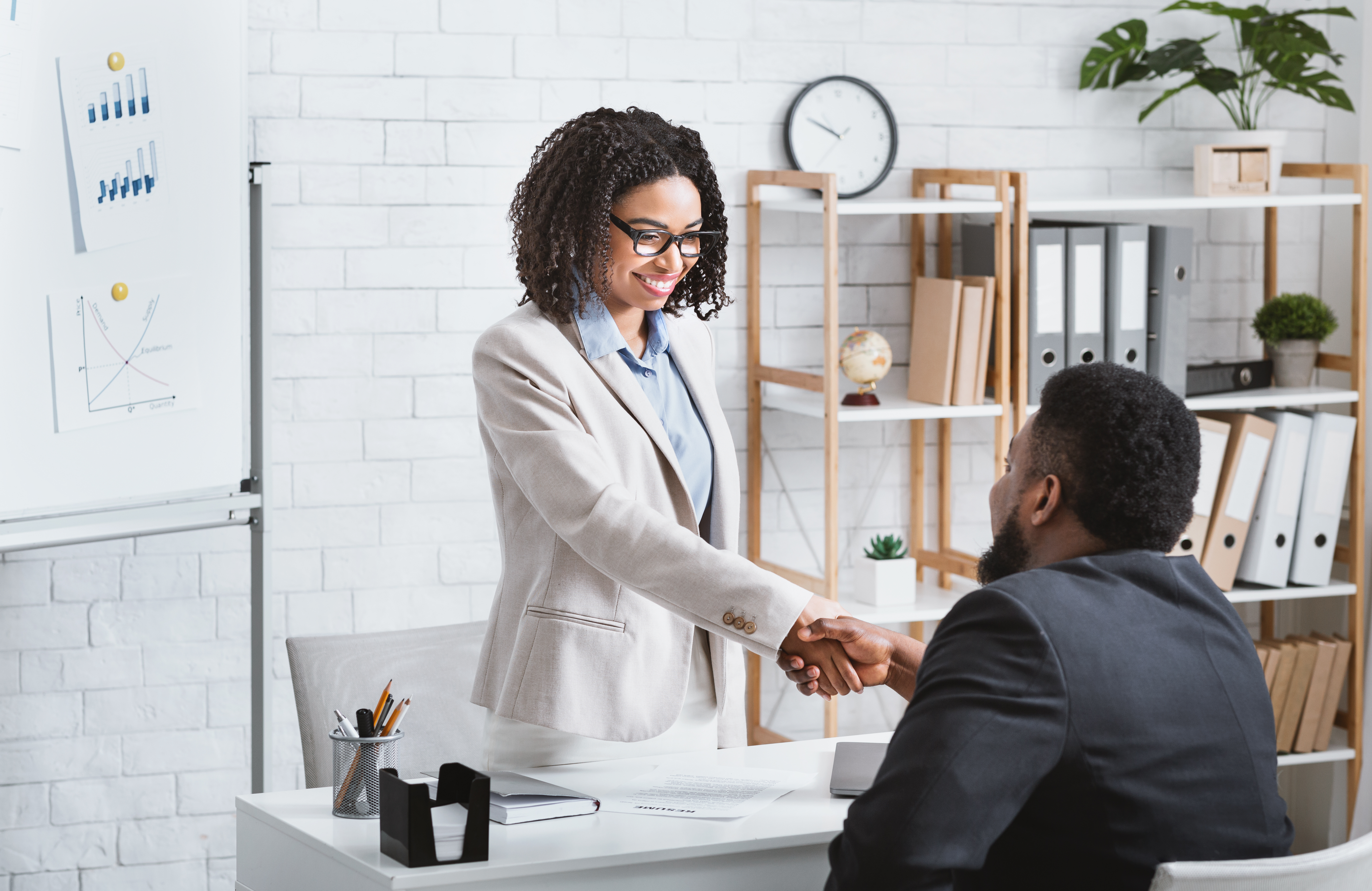 black-hiring-manager-shaking-hands-with-successful-CMKXBW6