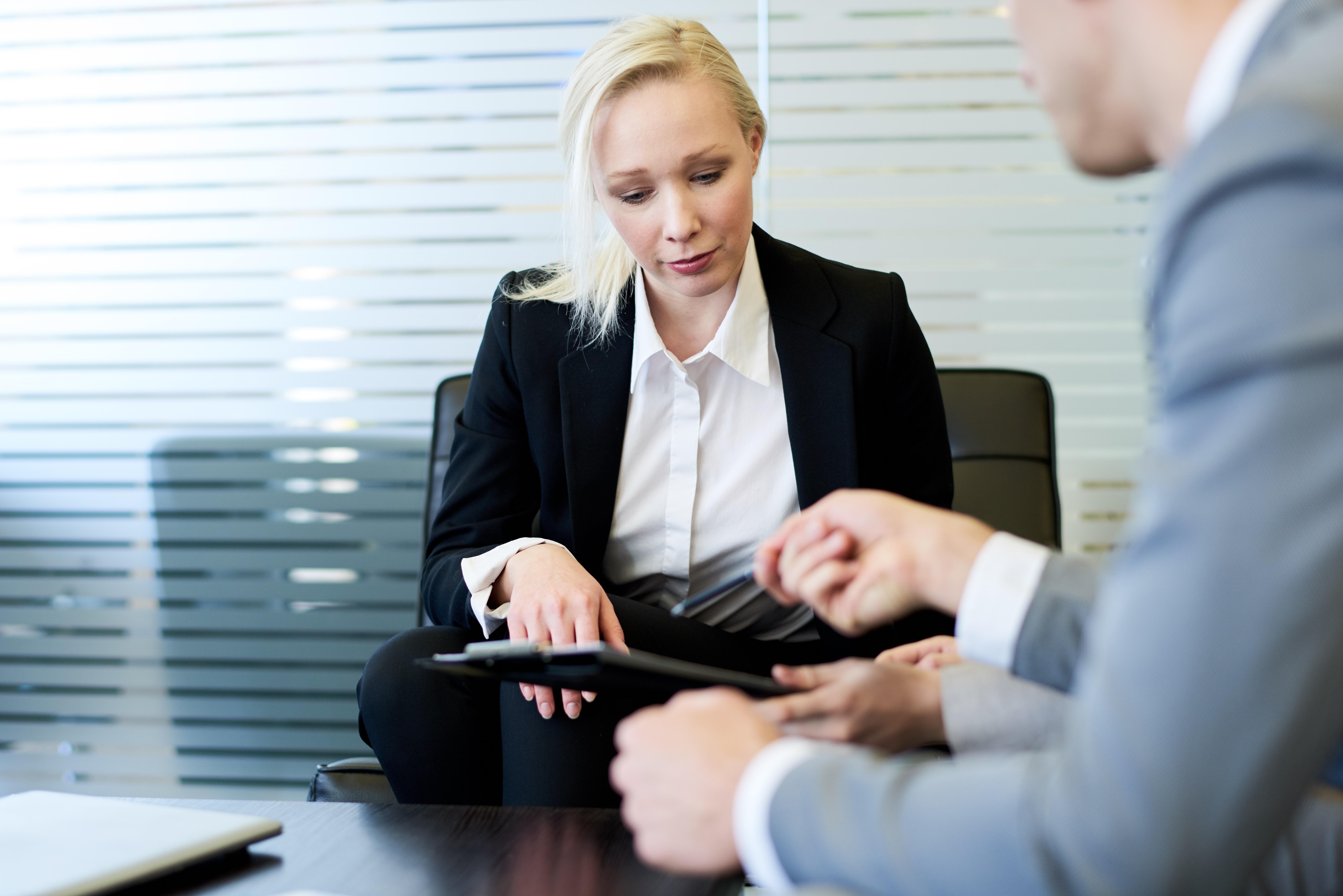 female-boss-reviewing-report-FM54USR