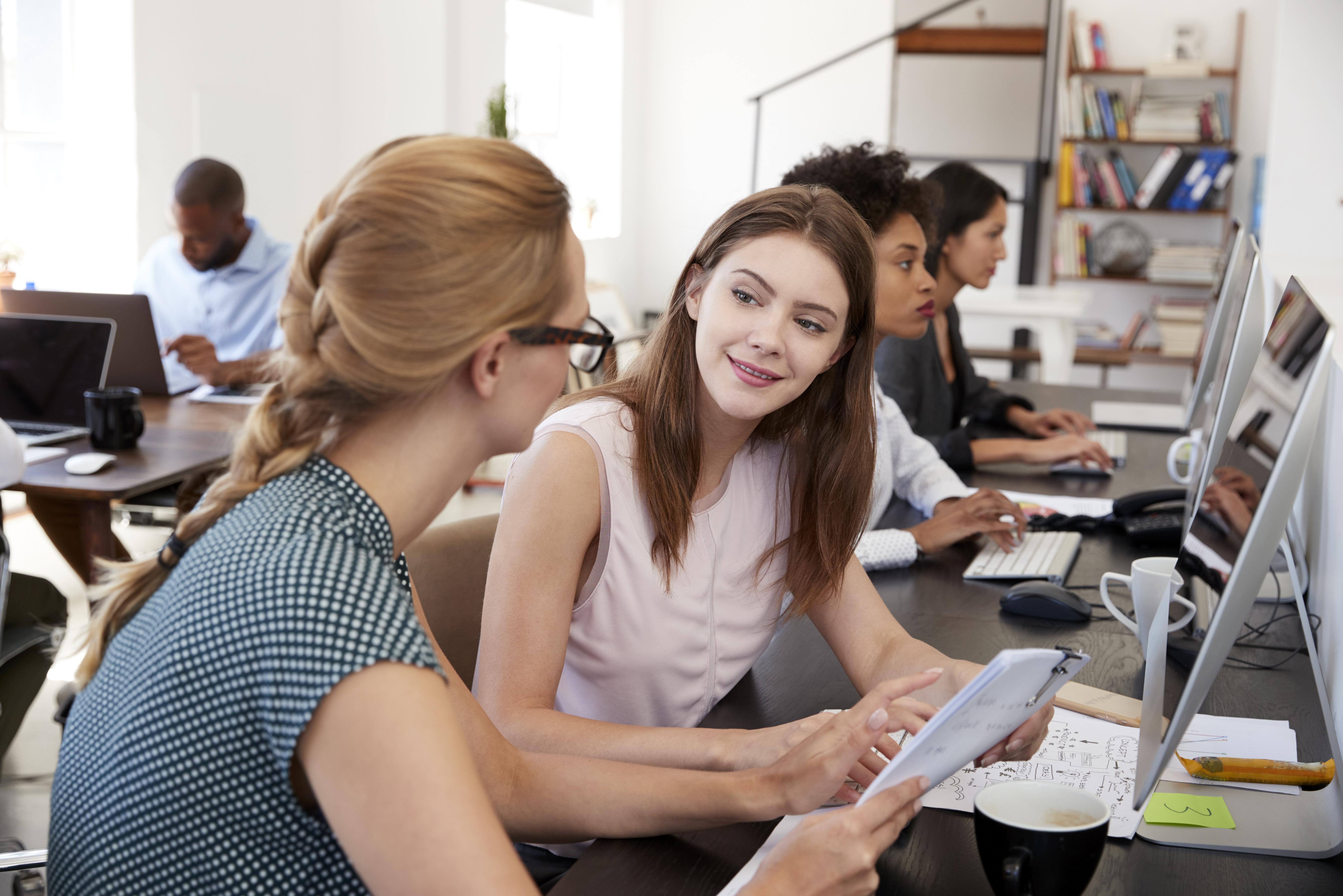 woman-training-new-female-employee-in-an-open-plan-PAJTWLU